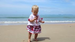 Girl in Ukrainian Costume Embroidery on Beach. Little girl in the national Ukrainian costume embroidery stands with a stone in hand on the beach stock video footage