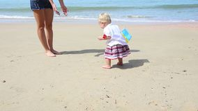 Girl in Ukrainian Costume Embroidery on Beach. Little girl in the national Ukrainian costume embroidery walking on the beach with a flag and mother stock footage