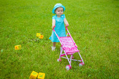 Little girl on nature with baby carriage Stock Photography