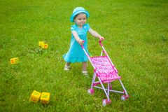 Little girl on nature with baby carriage Royalty Free Stock Photos
