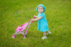 Little girl on nature with baby carriage Royalty Free Stock Photography
