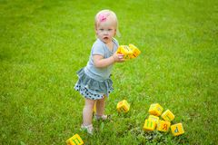 Little girl on nature playing toy Royalty Free Stock Image