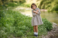 Little girl in nature stream wearing beautiful dress Stock Photo