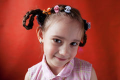 The little girl naughty school age. On an orange background Royalty Free Stock Photos