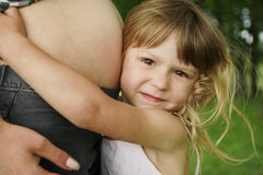 Little girl near the belly of his pregnant mother on nature Stock Photos