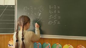 Little girl near the board decides the calculations