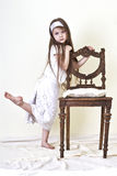 Little girl is near the chair Stock Photo