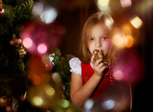 Little girl near Christmas tree. Sorrowful little girl near Christmas tree with magic irradiance or highlights Royalty Free Stock Photo