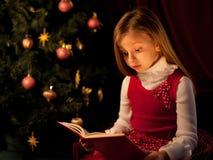 Little girl near Christmas tree. Reading book Stock Images