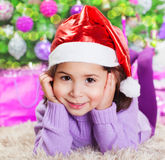 Little girl near Christmas tree. Closeup portrait of cute little girl lying down on carpet under beautiful decorated Christmas tree at home, winter holidays, New Royalty Free Stock Photography