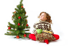 Little girl near the Christmas tree with cookies, a pillow Royalty Free Stock Photos