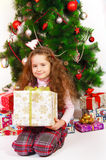 Little girl near the Christmas tree with gifts Stock Images