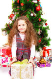 Little girl near the Christmas tree with gifts Royalty Free Stock Image