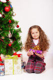 Little girl near the Christmas tree with gifts Stock Photos