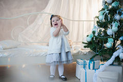 Little girl near Christmas tree with presents rejoices holiday, new year, decorations, gift, box, holiday, lifestyle Royalty Free Stock Images