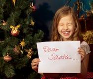 Little girl near Christmas tree  writing letter for Santa Stock Image