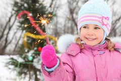 Little girl near christmass tree with bengal light Royalty Free Stock Photos
