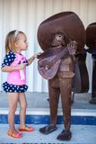 Little girl near figure of Mexican musician on the Royalty Free Stock Photos