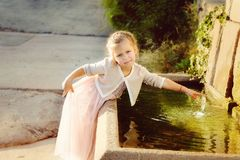 Little girl near the fountain Royalty Free Stock Photo