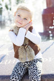 Little girl near fountain, autumn time Stock Images