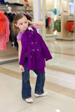 Little girl near a mirror try on clothes in store Royalty Free Stock Image