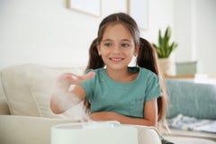 Little girl near air humidifier at home