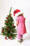 Little girl near New Year tree. Little girl standing near New Year tree and decorate it Stock Images