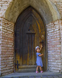 Little girl near the old fashioned door of the church Royalty Free Stock Photo