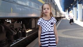 Little girl near a train. Little girl in a striped dress with a train near. girl was tired, she was not smiling stock video footage