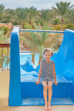 Little girl near water park slides Stock Photo