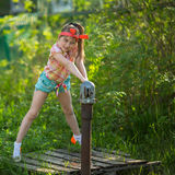 Little girl near the water pump in the village. Royalty Free Stock Photography