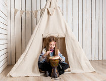 Little girl near wigwam playing Indian Stock Photos