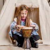 Little girl near wigwam playing Indian Stock Images