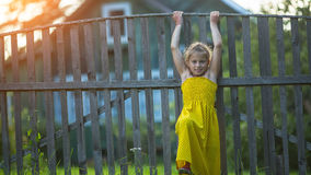 Little girl near the wood fence of a village house. Happy. Stock Photography