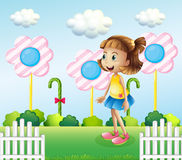 A little girl near the wooden fence with giant candies Royalty Free Stock Images