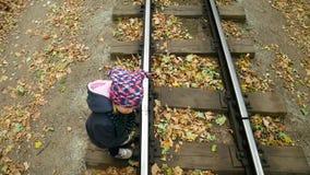 The little girl neatly crosses the railway. Video from the top point. The little girl neatly crosses the railway. Video from the top point stock footage