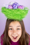 Little girl and nest with Easter eggs over her head Royalty Free Stock Image