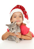 Little girl in New Year's cap with a kitten. Royalty Free Stock Images