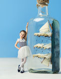 Little girl next to a ship in a bottle Stock Photo