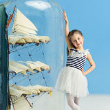 Little girl next to a ship in a bottle Stock Images