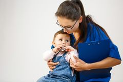 Little girl nibbles on a stethoscope and looks at the doctor royalty free stock image