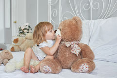 Little girl with a nice light brown teddy bear on white bed early in the morning Royalty Free Stock Image