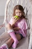 Small beautiful girl eating Apple green teeth royalty free stock photos
