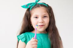 Little girl with no teeth with a toothbrush in dentistry stock photo
