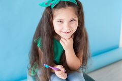 Little girl with no teeth with a toothbrush in dentistry royalty free stock photos