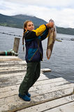 A little girl in Norway has a big fish in hand Royalty Free Stock Photos
