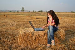 Little girl with notebook computer in field. Studies royalty free stock photo