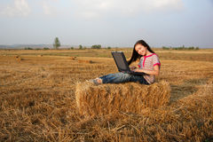 Little girl with notebook computer in field. Studies royalty free stock image