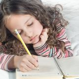 Little girl with notebook and pen Royalty Free Stock Images