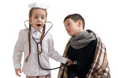 Little girl in nurse costume. Seasonal flu epidemic. Sick sad little boy wrapped in a blanket Stock Images